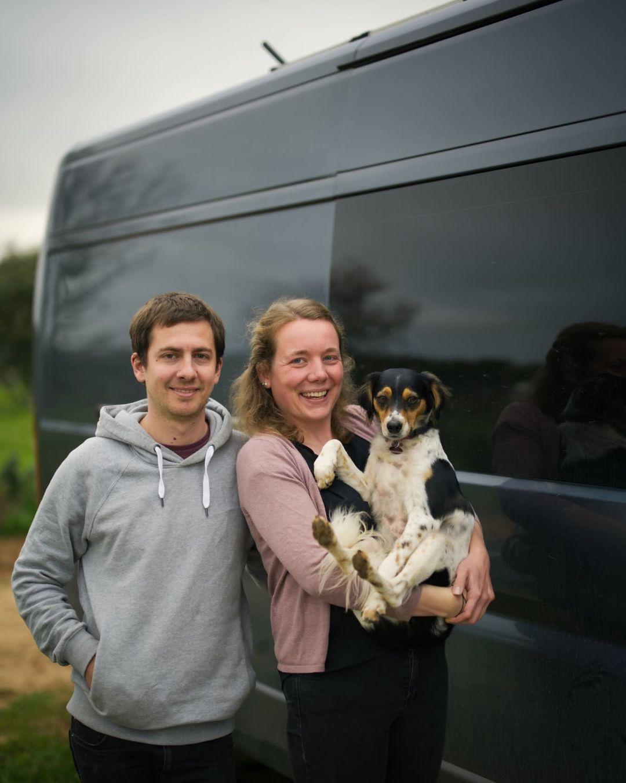 Zwei Menschen mit Hund vor ihrem Van