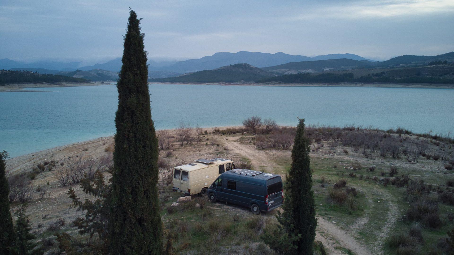 Zwei Camper Vans vor einem Stausee